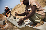A Chinese foreman helps a Guinean worker set the foundation of a wall in a straight line on the construction site of the Kipe hospital in Conakry, Guinea on Wednesday March 4, 2009. The Kipe hospital is a 10 million dollars project entirely funded by the Chinese government. (Olivier Asselin for the New York Times)
