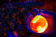 A glowing Christmas ornament being hung on a tree at night.Black light
