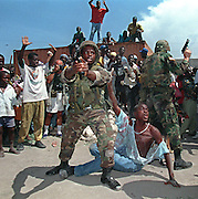 US Military Policemen pull their pistols to keep a crowd back as they protect a suspect in the hand grenade bombing of a pro-Aristide rally near the harbor in Port-au-Prince 29 September 1994. Witnesses to the bombing had tried to kill the man. Reportedly, three Haitians were killed and over twenty injured by the blast.