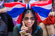 """20 DECEMBER 2013 - BANGKOK, THAILAND:  An anti-government protestor uses her smart phone during a demonstration in Bangkok. Many of the protestors are members of the Thai middle class, they are connected to the internet with smart phones and tablets. Thousands of anti-government protestors, supporters of the so called Peoples Democratic Reform Committee (PRDC), jammed the Silom area, the """"Wall Street"""" of Bangkok, Friday as a part of the ongoing protests against the caretaker government of Yingluck Shinawatra. Yingluck dissolved the Thai Parliament earlier this month and called for national elections on Feb. 2, 2014. The protestors want the elections postponed and the caretaker government to step down. The Thai election commission ruled Friday that the election would go on dispite the protests.         PHOTO BY JACK KURTZ"""