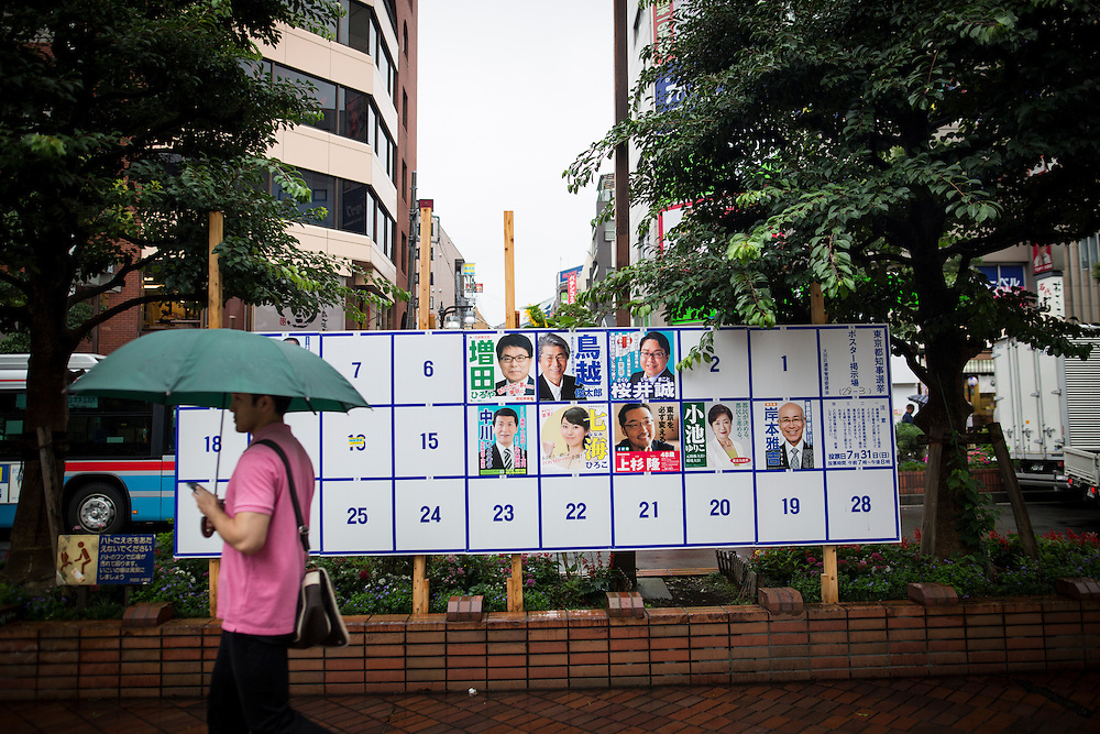 TOKYO, JAPAN - JULY 21 : A man walk past at campaign posters with pictures of candidates for the Tokyo Gubernatorial Election 2016 at Omori station, Tokyo, Japan on Thursday, July 21, 2016. Tokyo residents will vote on July 31 for a new Governor of Tokyo who will deal with issues related to the hosting of the Tokyo Summer Olympics and Paralympics in 2020. (Photo: Richard Atrero de Guzman/NUR Photo)