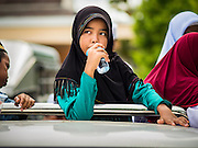 14 JUNE 2015 - NARATHIWAT, NARATHIWAT, THAILAND:  A Thai Muslim student drinks a cup of water in a pickup truck before leaving a food distribution in Narathiwat. The food distribution is done every year before  Ramadan, which starts June 18. The annual food distribution event is organized by the Southern Peace Media Club, a group of Thai journalists who work in the southern provinces of Pattani, Narathiwat and Yala. An insurgency pitting Muslim extremists against the Thai government has rocked Thailand's southern three provinces since 2001. More than 6,000 people have been killed in the sectarian violence.   PHOTO BY JACK KURTZ