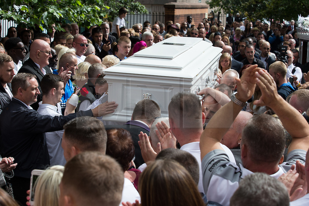"""© Licensed to London News Pictures . 28/08/2015 . Salford , UK . Paul Massey's coffin is carried in to the church as the crowd applauds . The funeral of Paul Massey at St Paul's CE Church in Salford . Massey , known as Salford's """" Mr Big """" , was shot dead at his home in Salford last month . Photo credit : Joel Goodman/LNP"""