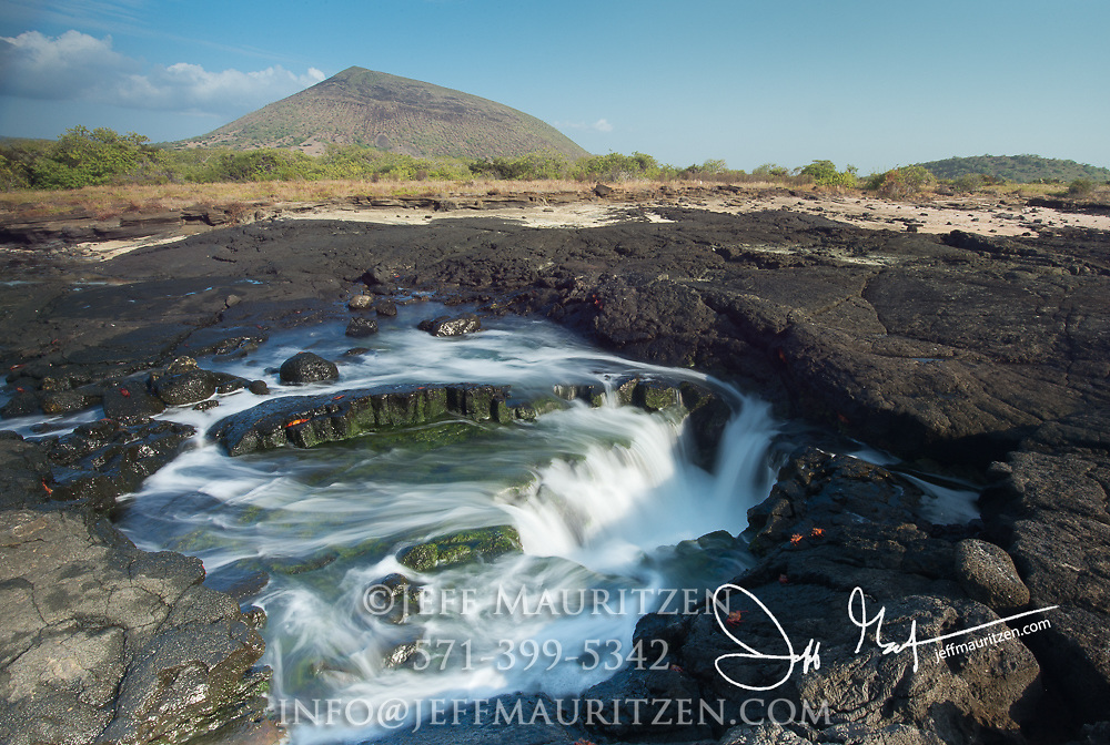 Water cascades in a tidal pool on Santiago island, Galapagos islands, Ecuador.