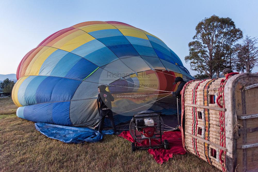 A hot air balloon pilot begins inflating a hot air balloon in San Miguel de Allende, Mexico.