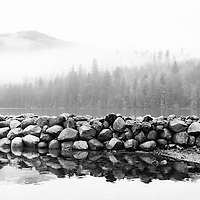 Landscape of rocks reflecting in the water with foggy forest in background.