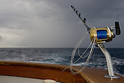 Single heavy tackle bent butt outfit with mono coils in teak covering board on a stormy day of trolling.