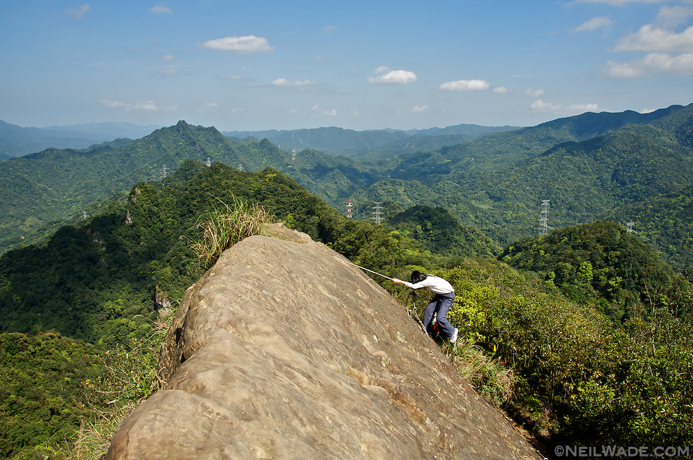 A hiker descends from a rocky, exposed peak in the mountains of northern Taiwan.