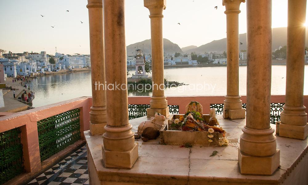 Sunrise on the holy Pushkar Lake, with pillars around an altar, India.