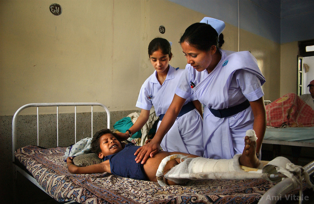 KATHMANDU, NEPAL, APRIL 14, 2004: Nepali nurses look after Sunil Sharma, 9 years old, in a hospital in Nepalganj, Nepal who was injured in an explosion 10 days earlier by Maoist insurgents fighting government forces April 14, 2004.  Over 8,000 people have been killed in the conflict and 2,000 of them have been children. (Ami Vitale/Getty Images)