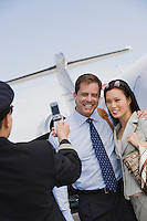 Airline pilot taking picture of businesswoman and businessman with mobile phone.