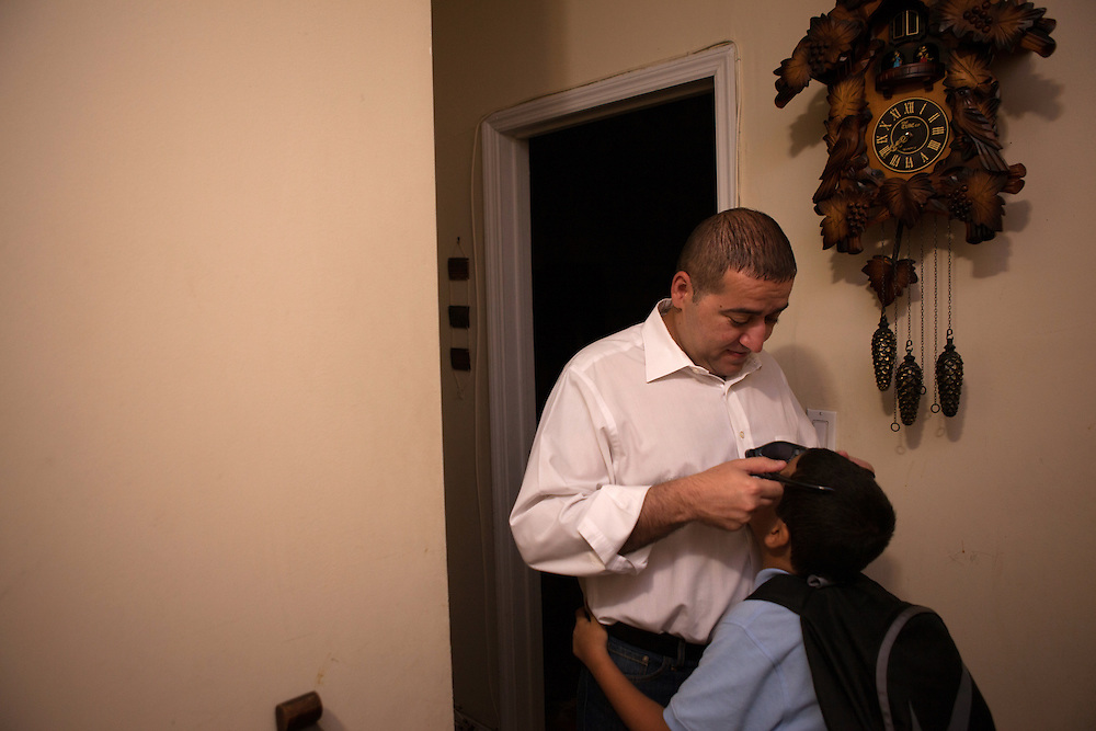 Saeid Haghighi helps his son Jesus Haghighi, 7, put on his sunglasses before school in their apartment in Fordham Heights in The Bronx, NY on September 11, 2013.