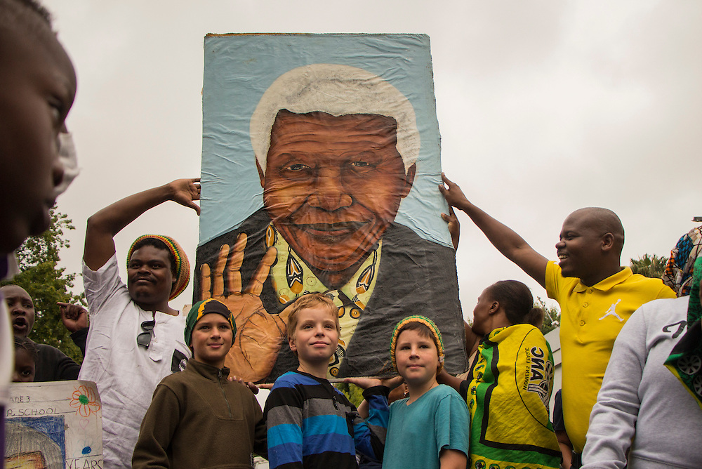 Three young South Africans are posing in front of a portrait of Nelson Mandela outside his house in Houghton, Johannesburg, on Friday Dec.6 2013.