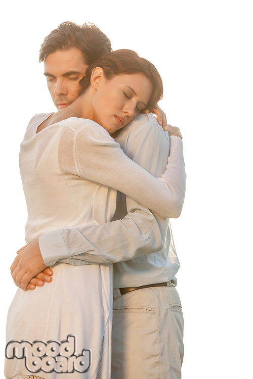 Affectionate young couple with eyes closed hugging in park against clear sky