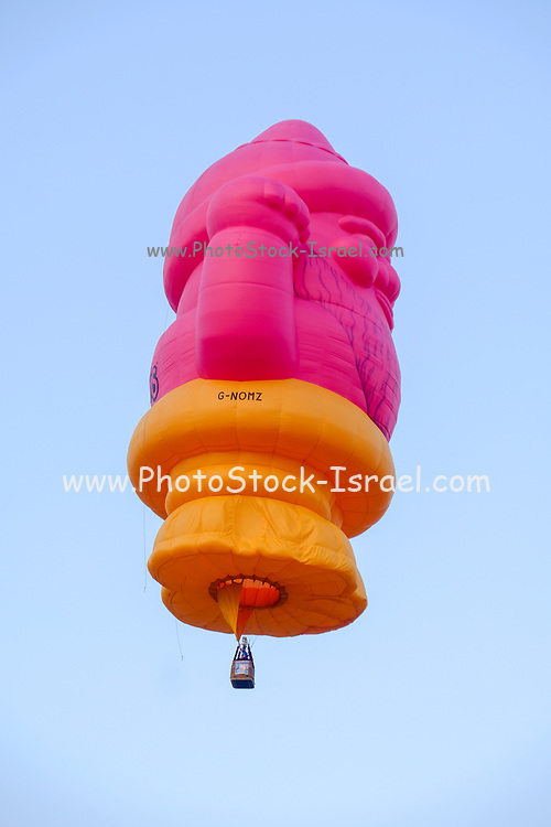 A decorated and elaborated hot air balloon rising with a blue sky background