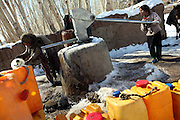 Hamidah, 6, (Left) and her two sisters Fatemah, 12, and Halemah, 9, are collecting water from a hand-pump situated on ground level a few hundred's meters from the cave where they live with their family since seven years, during a cold winter morning in Bamyan, central Afghanistan, an area mostly populated by Hazaras. A historically persecuted minority (15%) due to more lenient Islamic faith and characteristic 'Eastern' lineaments, Hazaras constitute the 70% of Bamyan's population.
