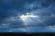 Rays of the sun break through a gap in the cloud in cloudy stormy sky during inclement weather giving a hint of sunlight, UK