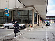 """20 MARCH 2020 - DES MOINES, IOWA: A jogger runs through the deserted streets of Des Moines. Most of downtown Des Moines is empty as businesses move to work at home and more businesses have employees who test positive for COVID-19. On Friday morning, 20 March, Iowa reported 45 confirmed cases of the Coronavirus. Restaurants, bars, movie theaters, places that draw crowds are closed for at least 30 days. There are no """"shelter in place"""" orders in effect anywhere in Iowa but people are being encouraged to practice """"social distancing"""" and many businesses are requiring or encouraging employees to telecommute.       PHOTO BY JACK KURTZ"""