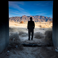 man standing at the threshold of the manmade and the nautral landscapes conjuring notions of environmental contrast.taken near the sandia mountains of albuquerque, new mexico.