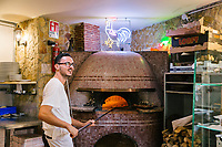 NAPLES, ITALY - 1 AUGUST 2018: Luigi, a pizzaiolo (pizza-maker), is seen here at work at Cantina del Gallo, a family-owned restaurant in the Rione Sanità in Naples, Italy, on August 1st 2018.<br /> <br /> Cantina del Gallo, in the Rione Sanità, was established in 1898 and run by four generations of the Silvestri family. The cantina began as a store selling bulk wine and oil. It was only in the 1950s, when the legendary Aunt Cuncetta began cooking, that it became the simple and genuine tavern it is today.<br /> There are three dishes that are the restaurant's workhorses, and the ones we always seem to rotate between: the pennette alla sorrentina (a variation of the classic gnocchi alla sorrentina, seasoned with tomato, basil and stringy mozzarella), the baked cod (although the fried cod is just as mouth-watering) and the pizza cafona (peasant pizza), topped with oregano, cheese, chile and with double the tomatoes (tomato juice and chopped tomatoes).