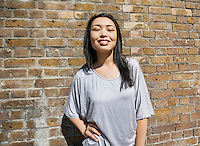 Portrait of confident young woman standing with hand on hip against brick wall
