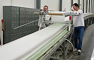 Tim Berger and Jerry Summers (from left) roll on a layer of fiberglass on a wind turbine blade at TPI Composites in Newton, Iowa on February 12, 2010.