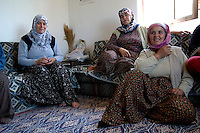 Turkish village women relaxing inside after working in greenhouses picking fruit and vegetables.