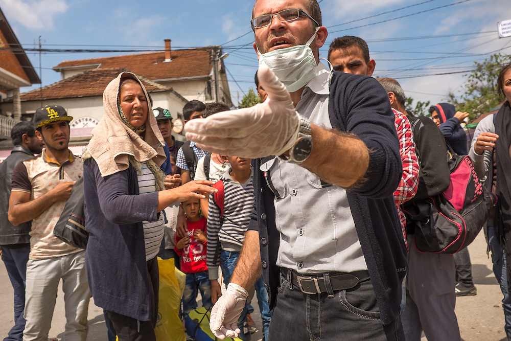 An UNHCR worker directs Syrian refugees at the Serbian Refugee Intake Center at Presevo, Serbia, on the border with Macedonia.
