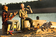 Lake Hemet CA for Wrangler of two boys ejoying camping on lakes edge at sunset roasting marsh mellows over campfire.