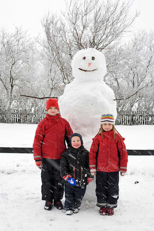 Proud group of kids in winterclothes standing by their snowman. Snow falling on ground. Trees in background...Krakkarnir stolltir við stóran snjókarl sem þau gerðu ásamt pabba.