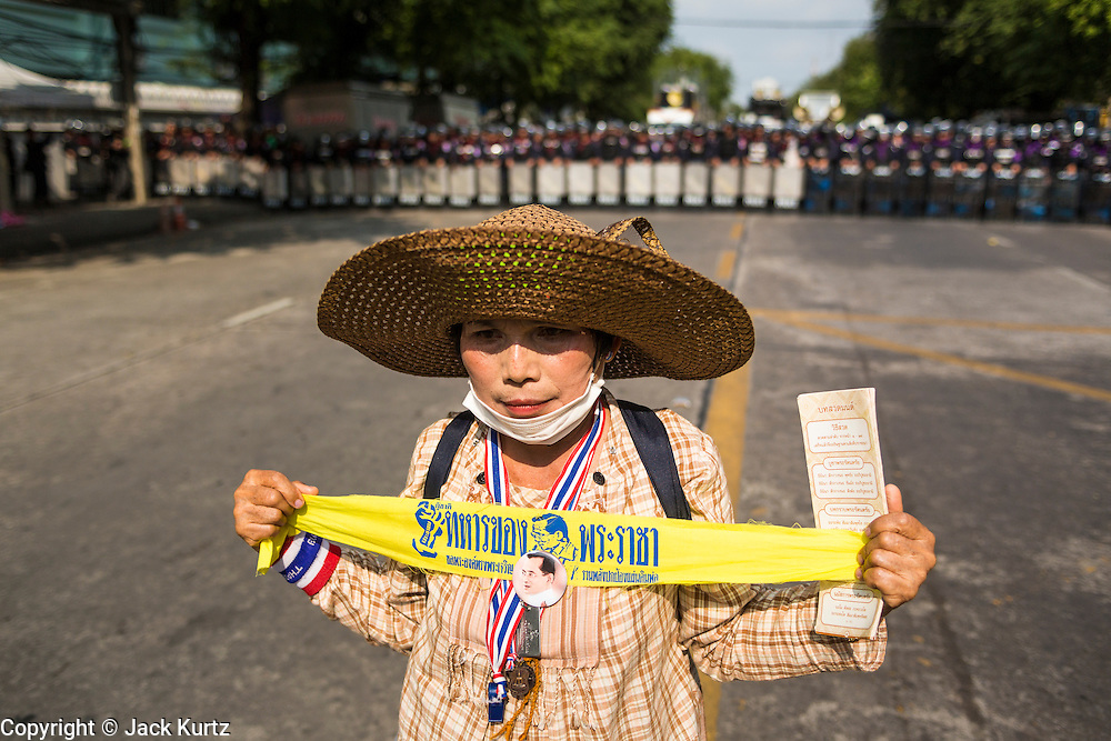 18 FEBRUARY 2014 - BANGKOK, THAILAND:  A Thai woman with a banner supporting Bhumibol Adulyadej, the King of Thailand, stands in front of a line of police officers during a protest at Government House in Bangkok. Anti-government protestors aligned with Suthep Thaugsuban and the People's Democratic Reform Committee (PDRC) clashed with police Tuesday. Protestors opened fire on police with at rifles and handguns. Police returned fire with live ammunition and rubber bullets. The Bangkok Metropolitan Administration's Erawan Emergency Medical Centre reported that three civilians and a policeman were killed and 64 others were injured in the clashes between police and protesters.   PHOTO BY JACK KURTZ