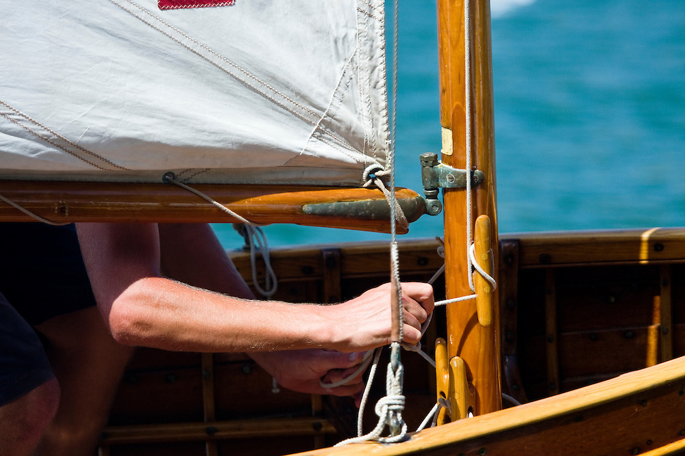 A hand secures a halyard on this little sailing dinghy in preparation for the annual gig  regatta which takes place on the final day of the 2008 Antigua Classic Yacht Regatta . This race is one of the worlds most prestigious traditional yacht races. It takes place annually off the cost of Antigua in the British West Indies. Antigua is a yachting haven, historically a British navy base in the times of Nelson.