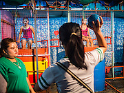 24 NOVEMBER 2015 - BANGKOK, THAILAND:  Girls in a dunk tank game at the Wat Saket temple fair. Wat Saket is on a man-made hill in the historic section of Bangkok. The temple has golden spire that is 260 feet high which was the highest point in Bangkok for more than 100 years. The temple construction began in the 1800s in the reign of King Rama III and was completed in the reign of King Rama IV. The annual temple fair is held on the 12th lunar month, for nine days around the November full moon. During the fair a red cloth (reminiscent of a monk's robe) is placed around the Golden Mount while the temple grounds hosts Thai traditional theatre, food stalls and traditional shows.       PHOTO BY JACK KURTZ