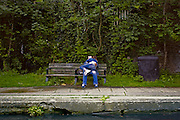 Pair of lovers snuggle on a bench alongside the Regent's Canal.