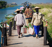 Women walking on pier after shopping at local market in Inle Lake (Myanmar)