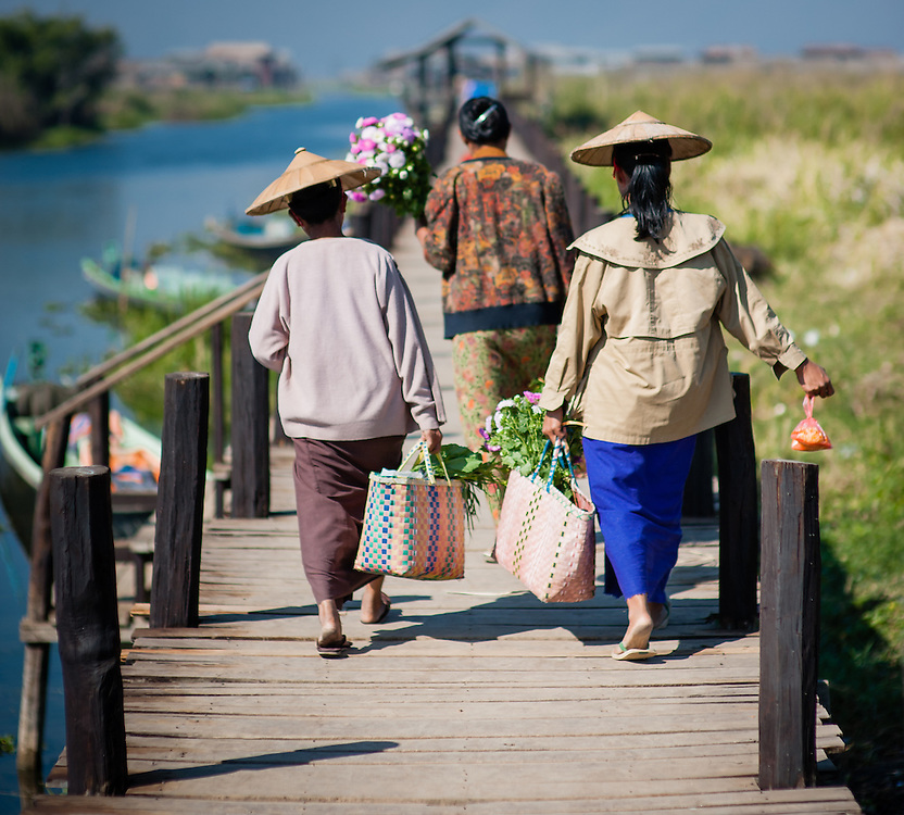 Women walking on pier after shopping at local market in Inle Lake (Myanmar)