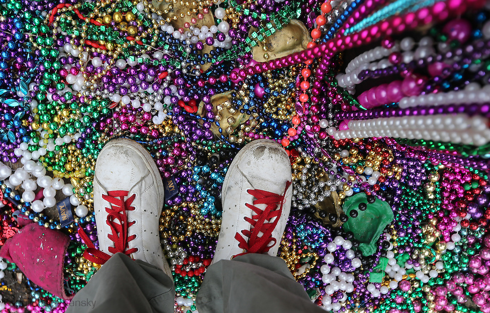 New Orleans, LA, February 12, 2013, Sneakers with red shoelaces  stand on Mardi Gras beads in the French Quarter on Fat Tuesday, Mardi Gras Day. On Fat Tuesday, parades roll down St. Charles Ave. and people flock to the French Quarter and the Marigny for a day of celebrating in the streets before Ash Wednesday.