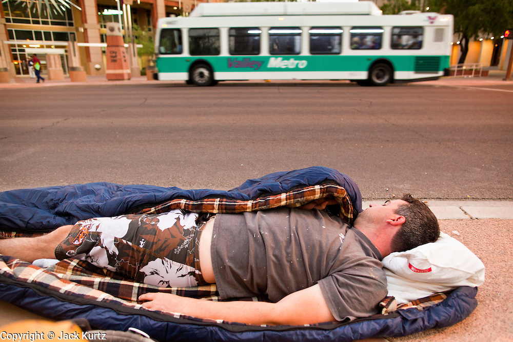 17 OCTOBER 2011 - PHOENIX, AZ:   BRIAN KORSEDAL, from Phoenix, AZ, sleeps on the sidewalk during the Occupy Phoenix protest Monday. About 40 people spent Sunday night on the sidewalks around the Cesar Chavez Plaza in Phoenix, AZ, the defacto headquarters of the Occupy Phoenix protest. Early Monday morning they got up to continue their chants and protests against Wall Street, the growing income gap between rich and poor in the US, and money in politics. Monday marks the third day of Occupy Phoenix.    PHOTO BY JACK KURTZ