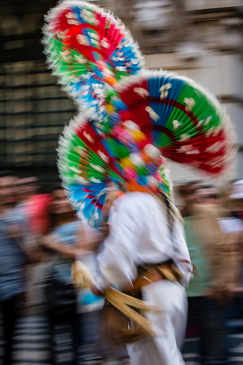 These strange masks from the region of Leon, Spain, show headwear made of colorful paper and cloth, which produce a stunning effect as the masked men run and jump up and down.