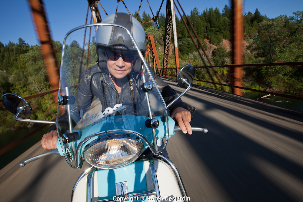 Woman on Vespa motor scooter riding on bridge over Russian River in Sonoma County, California. http://www.gettyimages.com/detail/news-photo/mature-woman-riding-motor-scooter-over-bridge-on-country-news-photo/478958321