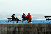 Locals sitting on benches on the Porporela (breakwater) at sundown, Dubrovnik old town, Croatia