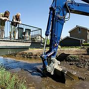 Nederland Krimpen aan den IJssel 30 mei 2007 20070530.Bewoner nieuwbouw woning kijkt hoe een watergang voor het pand wordt aangelegd  ..Serie tbv Schieland en de Krimpenerwaard, deze zorgt als waterschap voor droge voeten en schoon water in een bepaald gebied. Het beheersgebied van Schieland en de Krimpenerwaard strekt zich uit tussen Rotterdam, Schoonhoven en Zoetermeer. Binnen dit gebied zorgt Schieland en de Krimpenerwaard voor de kwaliteit van het oppervlaktewater, het waterpeil en de waterkeringen. Daarnaast beheert Schieland en de Krimpenerwaard een aantal wegen in de Krimpenerwaard...Foto David Rozing