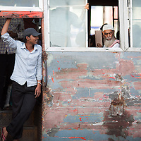 A bus conductor recognizes a friend as he works from the open door of the beaten and battered bus that is a part of Chittagong's chaotic public transport system.