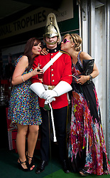 LIVERPOOL, ENGLAND - Friday, April 9, 2010: Ashley Long from Liverpool and Sarah Wilsey from Belfast pose with a soldier from the Duke of York Regiment on Ladies' Day during the second day of the Grand National Festival at Aintree Racecourse. (Pic by David Rawcliffe/Propaganda)