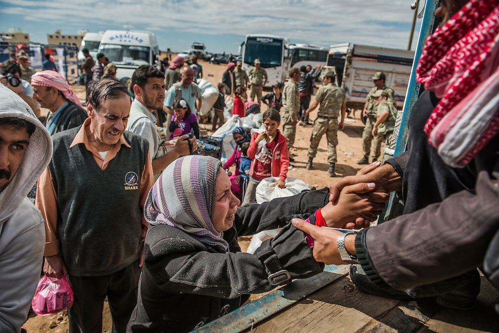 Syrian Kurdish people get into bus after crossing the border between Syria and Turkey after several mortars hit both side in the southeastern town of Suruc, in the Sanliurfa province, on September 30, 2014.