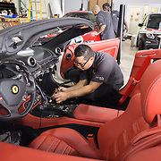 DORAL, FLORIDA, DECEMBER 11, 2015<br /> Jose Oyuela works on the sound system of a Ferrari California, a Christmas present from a professional baseball player to his wife, in the garage of The Auto Firm, a South Florida car customizing and restoring shop which has a vast clientele of professional athletes and entertainers.<br /> (Photo by Angel Valentin/Freelance)