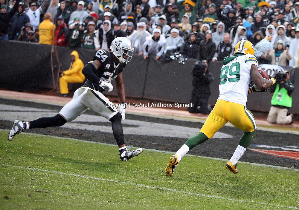 Green Bay Packers wide receiver James Jones (89) catches a 30 yard touchdown pass good for a 24-20 third quarter Packers lead while being chased by Oakland Raiders free safety Charles Woodson (24) during the 2015 week 15 regular season NFL football game against the Oakland Raiders on Sunday, Dec. 20, 2015 in Oakland, Calif. The Packers won the game 30-20. (©Paul Anthony Spinelli)