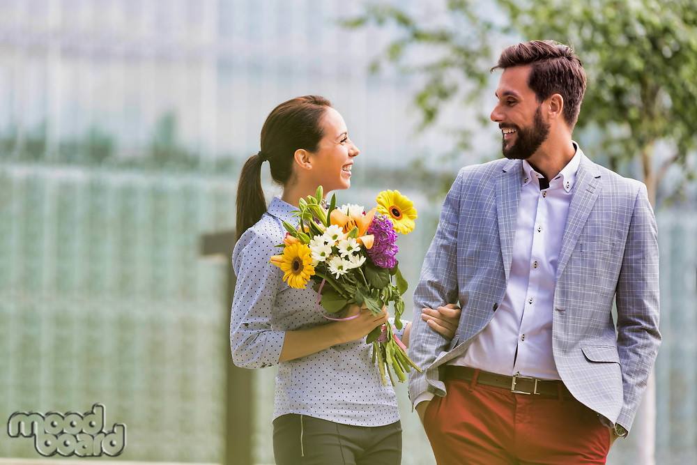 Young attractive business couple walking in park while the woman is holding boquet of flowers