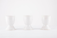 Three empty egg cups side by side over white background