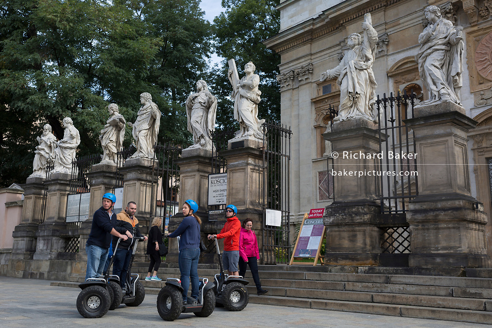 Tourists on Segways listen to their tour guide beneath the statues of twelve apostle outside the church St. Peter and St. Paul Church on Grodzka street, on 23rd September 2019, in Krakow, Malopolska, Poland.